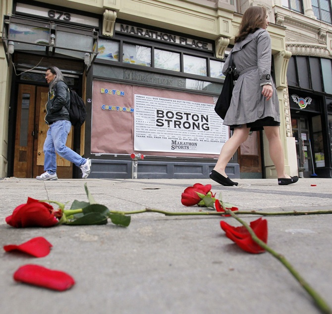 Flowers lie on the sidewalk at the site of the first explosion as people walk along Boylston   Street after the street reopened to the public for the first time since the Boston Marathon bombings in Boston