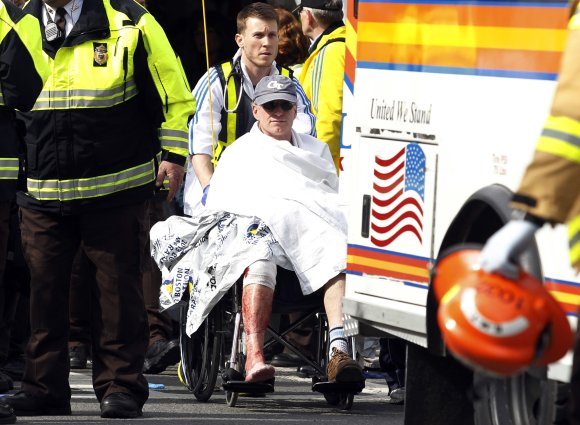 A runner in a wheelchair is taken from a triage tent after explosions went off at the 117th Boston Marathon in Boston