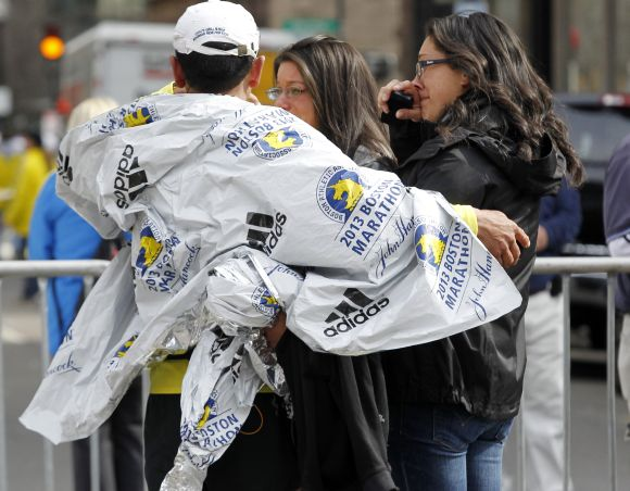 People comfort each other after explosions went off at the 117th Boston Marathon in Boston
