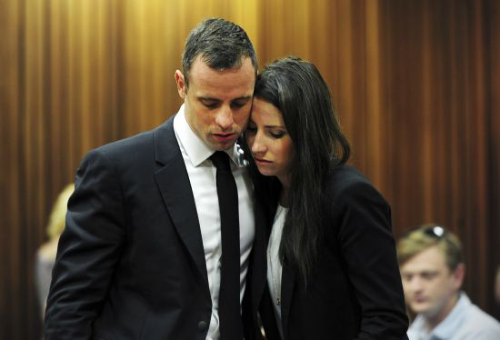 Olympic and Paralympic track star Oscar Pistorius stands beside his sister Aimee during court proceedings