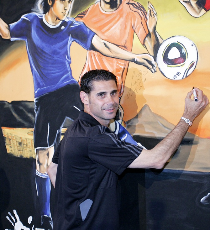 Fernando Hierro signs a painting during a media event