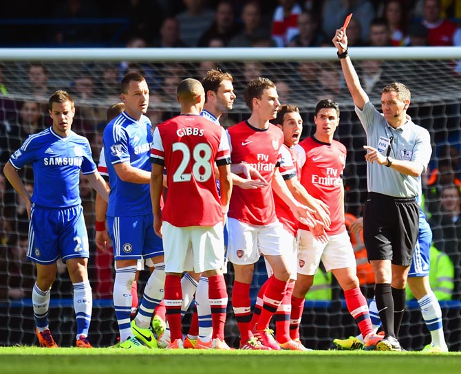 Referee Andre Marriner shows Kieran Gibbs of Arsenal a red card