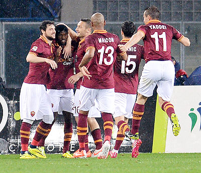 Gervinho of AS Roma is mobbed by teammates after scoring his team's opening goal against AC Chievo Verona during their Serie A match on Saturday