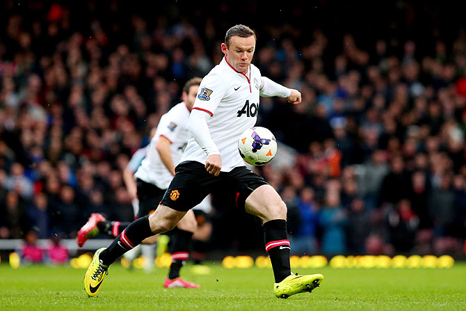 Wayne Rooney of Manchester United strikes to score the opening goal with a long range shot against West Ham United at Boleyn Ground in London on Saturday
