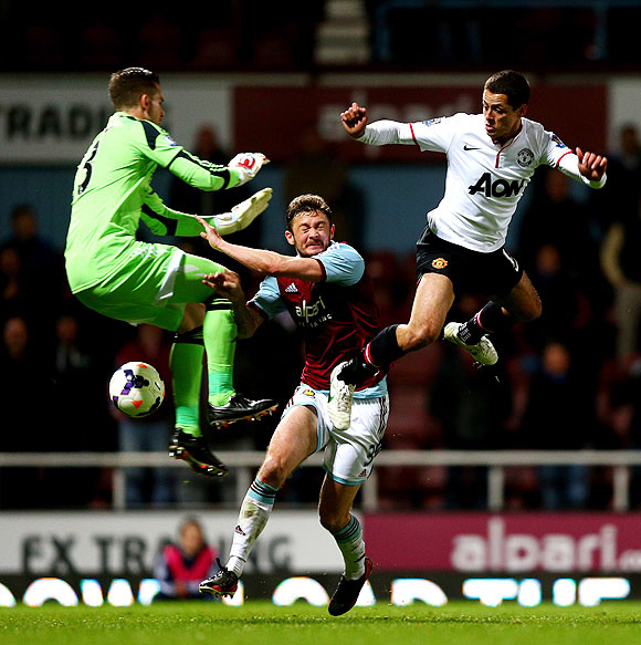 West Ham's goalkeeper Adrian and defender George McCartney compete for the ball against Manchester United's Javier Hernandez on Saturday