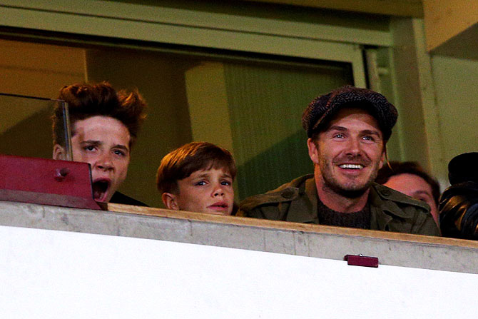 Former England and Manchester United player David Beckham and his sons Romeo and Brooklyn watch the action between West Ham United and Manchester United at Boleyn Ground in London on Saturday