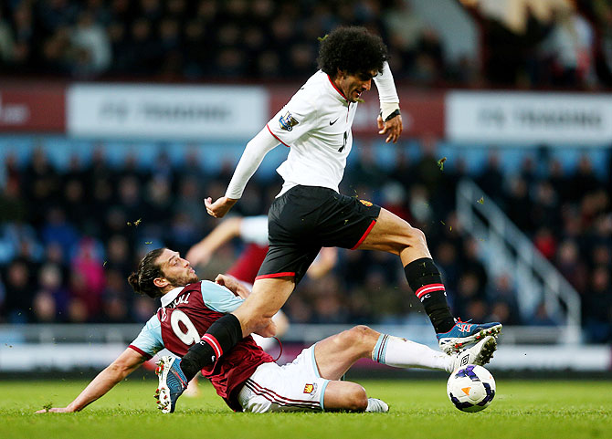 Marouane Fellaini of Manchester United is tackled by Andy Carroll of West Ham during their match on Saturday