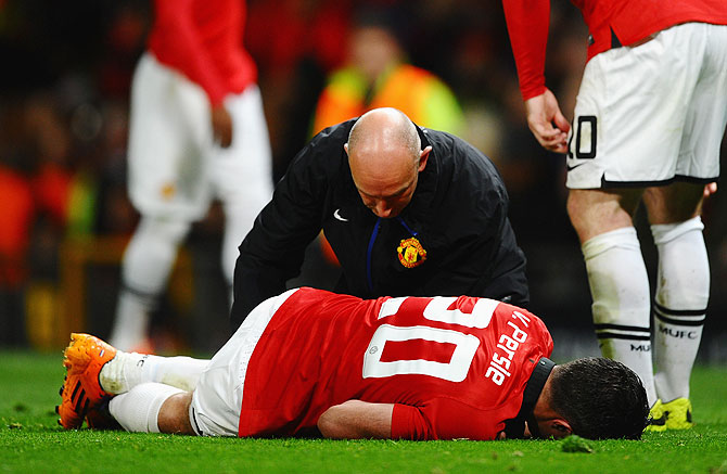 Robin van Persie of Manchester United receives treatment during the UEFA Champions League Round of 16 second round match against Olympiacos FC at Old Trafford