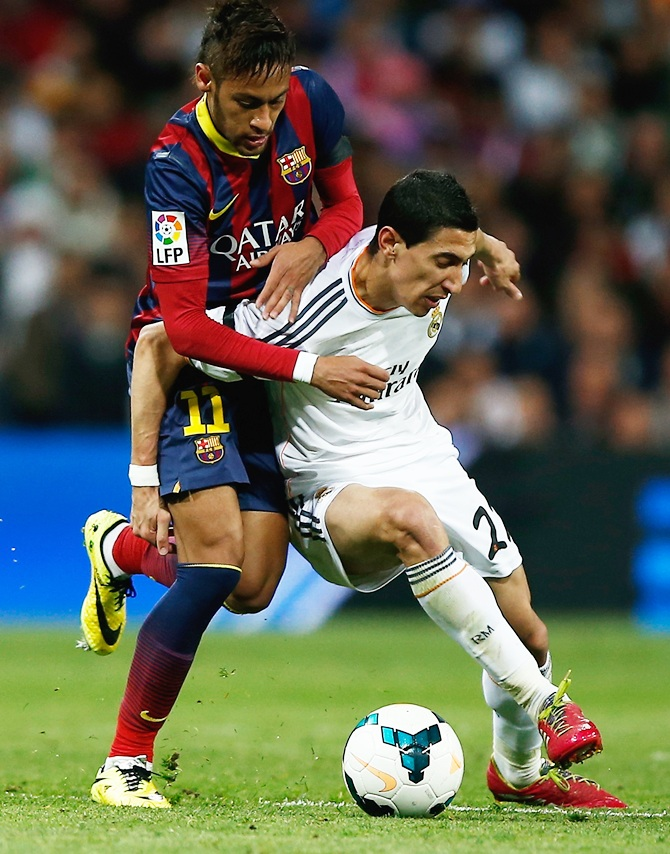 Angel Di Maria of Real Madrid is challenged by Neymar of Barcelona