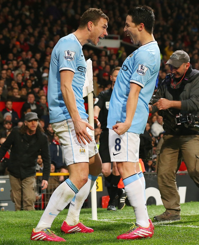 Edin Dzeko of Manchester City celebrates scoring the second goal with team-mate Samir Nasri