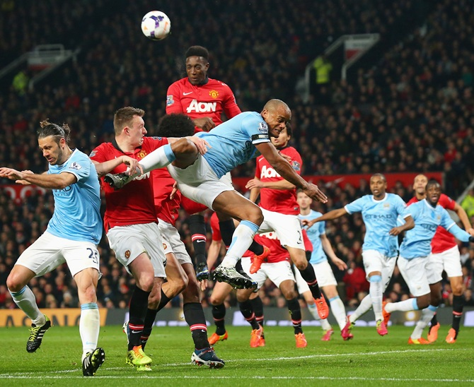 Vincent Kompany of Manchester City tangles with Phil Jones and Danny Welbeck of Manchester United