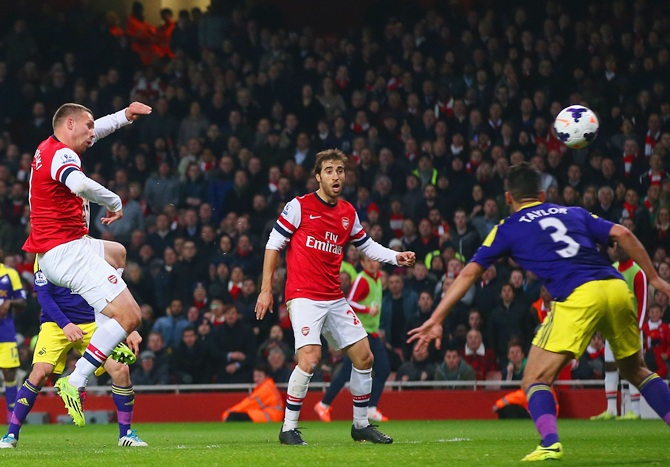 Lukas Podolski of Arsenal scores their first goal