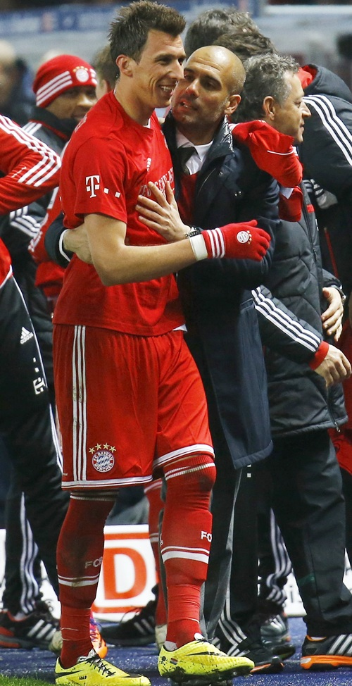 Bayern Munich's coach Pep Guardiola speaks with Mario Mandzukic,left, as they celebrate