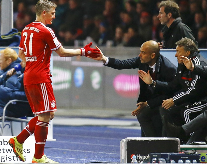 Bayern Munich's Bastian Schweinsteiger, left, claps hands with coach Pep Guardiola