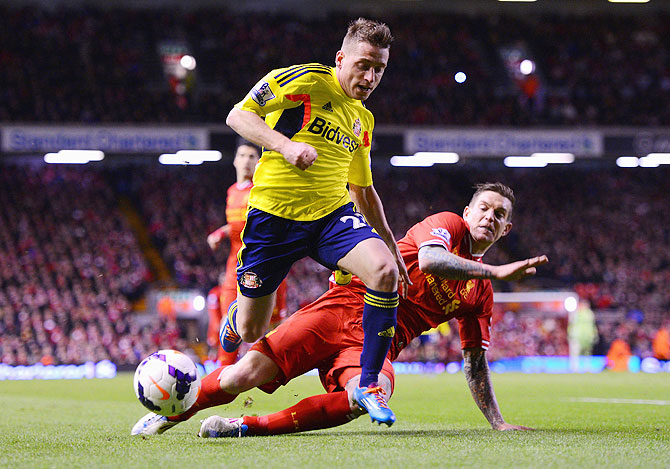 Daniel Agger of Liverpool challenges Emanuele Giaccherini of Sunderland during their match on Wednesday