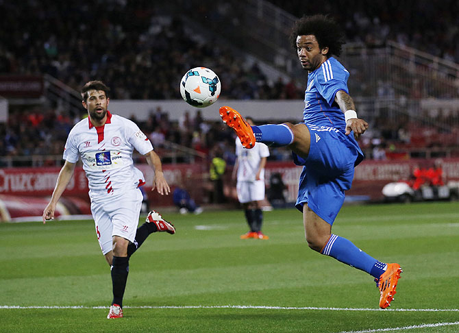 Real Madrid's Marcelo (right) beats Sevilla's Jorge Andujar to the ball during their La Liga match on Wednesday