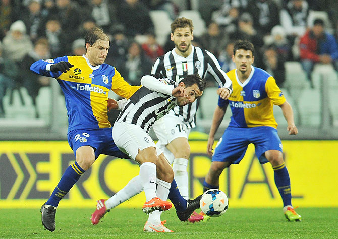Carlos Tevez (right) of Juventus is tackled by Gabriel Alejandro Paletta of Parma FC during the serie A match at Juventus Arena in Turin, Italy on Wednesday