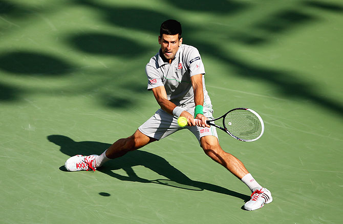 Novak Djokovic of Serbia stretches to play a backhand against Andy Murray of Great Britain during their quarter-final on Wednesday
