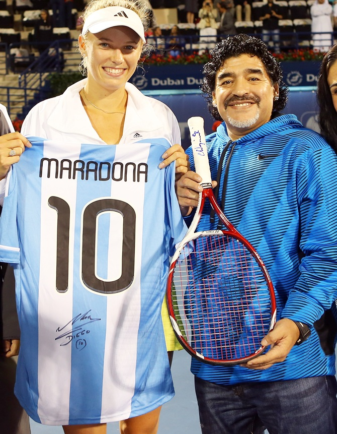 Caroline Wozniacki of Denmark exchanges gifts with football legend Diego Maradona