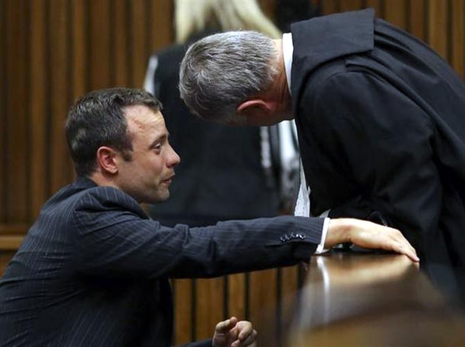 Oscar Pistorius (left) cries as he chats to his lawyer Barry Roux during his trial