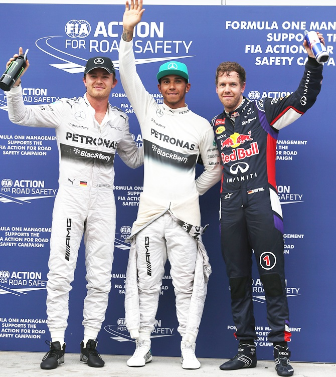 Lewis Hamilton of Great Britain and Mercedes GP,centre, celebrates   in parc ferme after finishing first alongside Sebastian Vettel,right, and Nico Rosberg