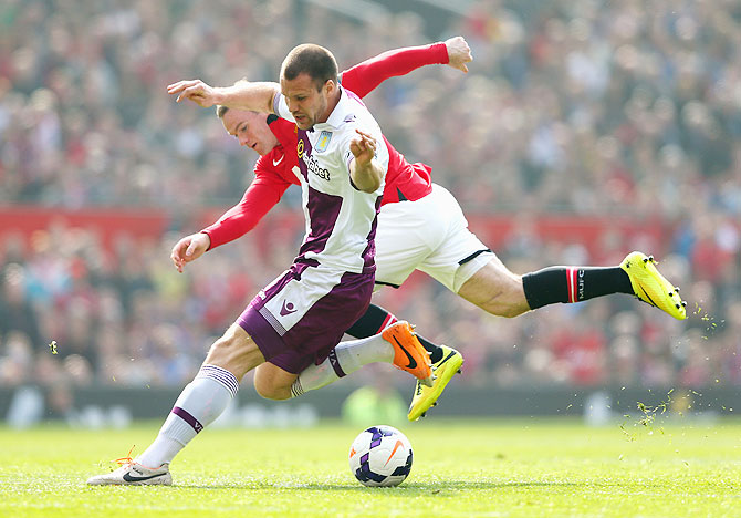 Wayne Rooney of Manchester United tangles with Ron Vlaar of Aston Villa during their English Premier League match on Saturday