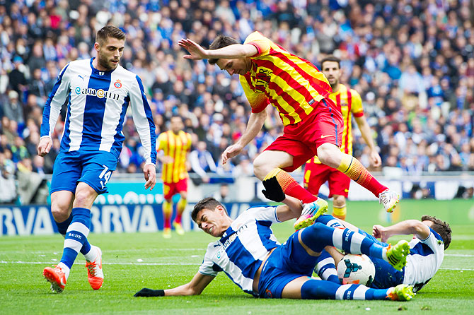 Lionel Messi of FC Barcelona fights for the ball with Hector Moreno and Cristhian Stuani as David Lopez of Espanyol watches during their La Liga match at Cornella-El Prat Stadium in Barcelona on Saturday