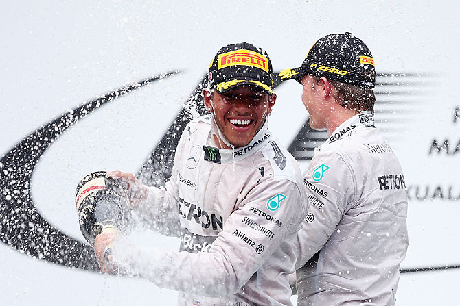 Race winner Lewis Hamilton and Mercedes GP (left) celebrates on the podium with teammate and second placed Nico Rosberg after the Malaysia Formula One Grand Prix at the Sepang Circuit in Kuala Lumpur on Sunday