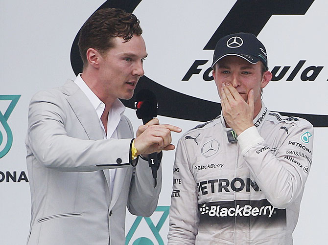 British actor Benedict Cumberbatch interviews second-placed Mercedes Formula One driver Nico Rosberg of Germany on the podium after the Malaysian F1 Grand Prix at Sepang International Circuit on Sunday