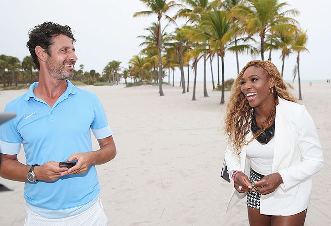 Serena Williams of the United States walks on Crandon Park beach and smiles to her coach and boyfriend Patrick Mouratoglou after her straight sets victory over Li Na of China on Saturday