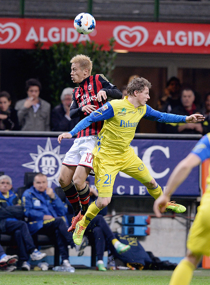 Keisuke Honda of AC Milan #10 and Nicolas Frey of AC Chievo Verona compete for the ball during their match on Saturday