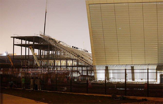 Workers look at the Arena Sao Paulo stadium, known as Arena Corinthians and Itaquerao, in Sao Paulo