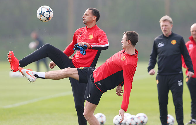 Rio Ferdinand and Jonny Evans of Manchester United compete for the ball as team manager David Moyes watches during a training session at the Aon Training Complex in Manchester on Monday