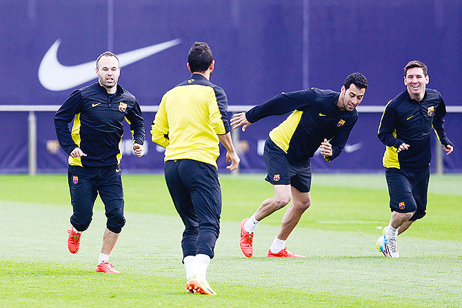 Barcelona's Andres Iniesta, Sergio Busquets and Lionel Messi warm up during a training session on Monday