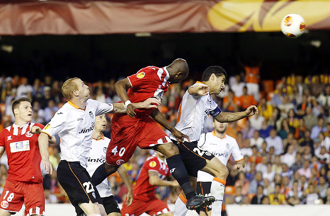 Sevilla's Stephane Mbia (centre) heads the ball to score past Jeremy Mathieu (2nd from left) and Ricardo Costa (right) of Valencia during their Europa League semi-final second leg match at Mestalla stadium in Valencia, on Thursday