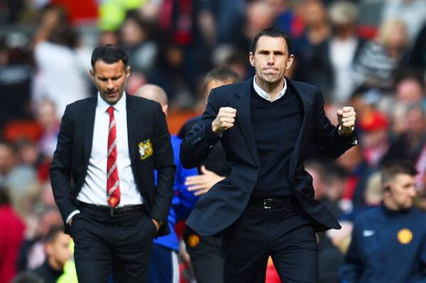 Sunderland manager Gustavo Poyet celebrates his team's 1-0 victory as a dejected Ryan Giggs, Manchester United's interim manager, walks behind.