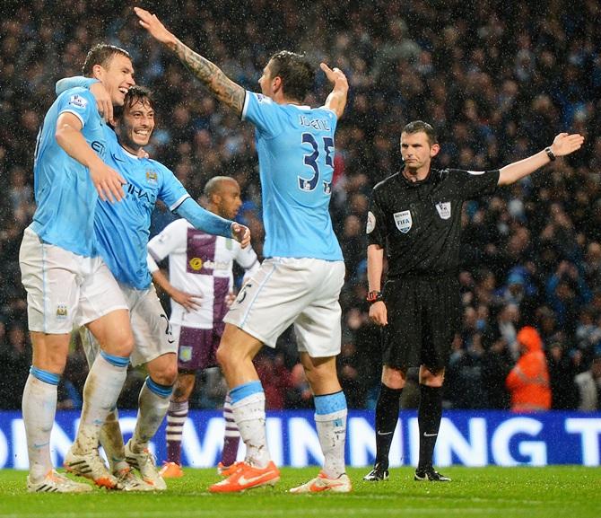 Edin Dzeko,left, of Manchester City celebrates scoring his team's second goal