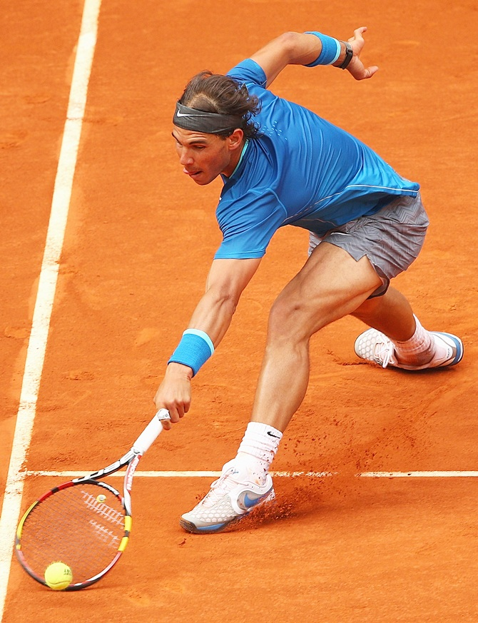 Rafael Nadal stretches to play a backhand volley against Juan Monaco