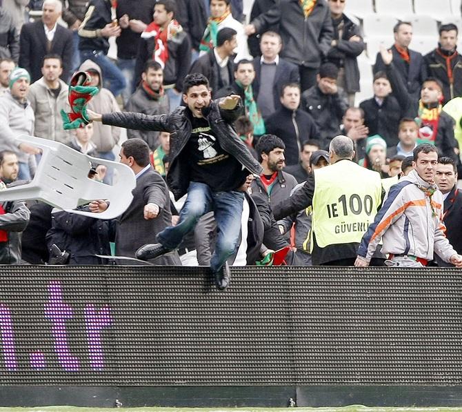 A fan jumps over a hoarding