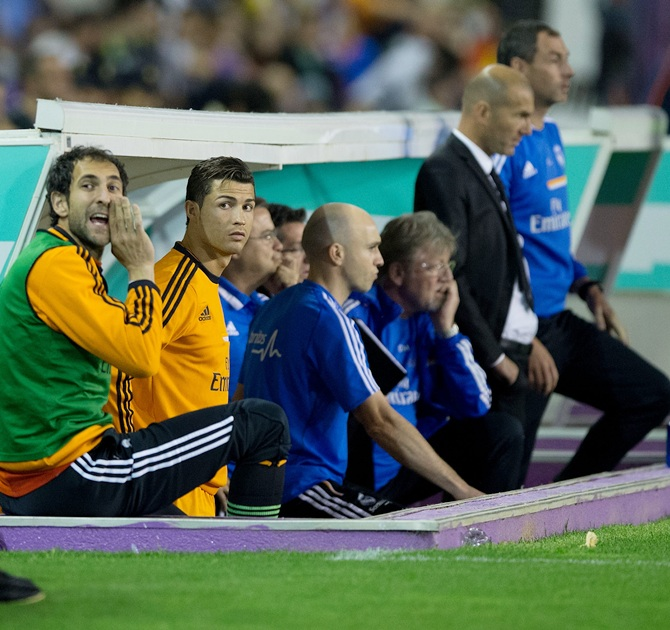 Goalkeeper Diego Lopez,left, of Real Madrid and his teammate Cristiano Ronaldo,right, watch the acton from the bench