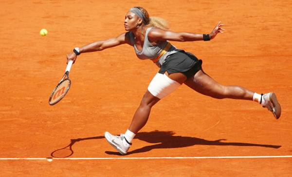 Serena Williams of the United States stretches to play a forehand against Carla Suarez Navarro of Spain in their third round of the Madrid Open.