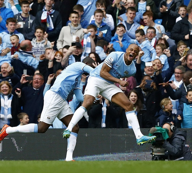 Manchester City's captain Vincent Kompany,right, celebrates after scoring against West Ham United