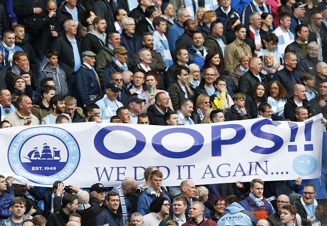 Manchester City fans hold a banner as their team take on West Ham United