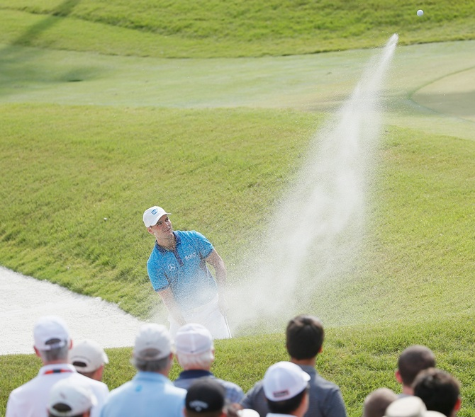 Martin Kaymer of Germany hits a bunker shot on the tenth hole
