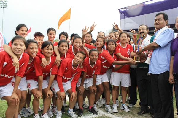 The Manipur players are all smiles as AIFF executive committee member Ankur Dutta presents the trophy to their captain, Bembem Devi.