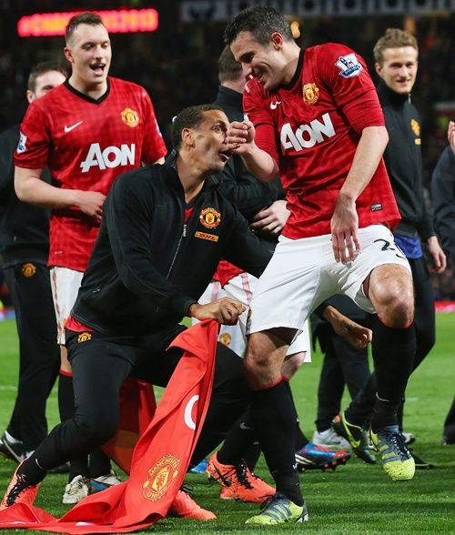 Rio Ferdinand of Manchester United tries to pull Robin van Persie's shorts as they celebrate