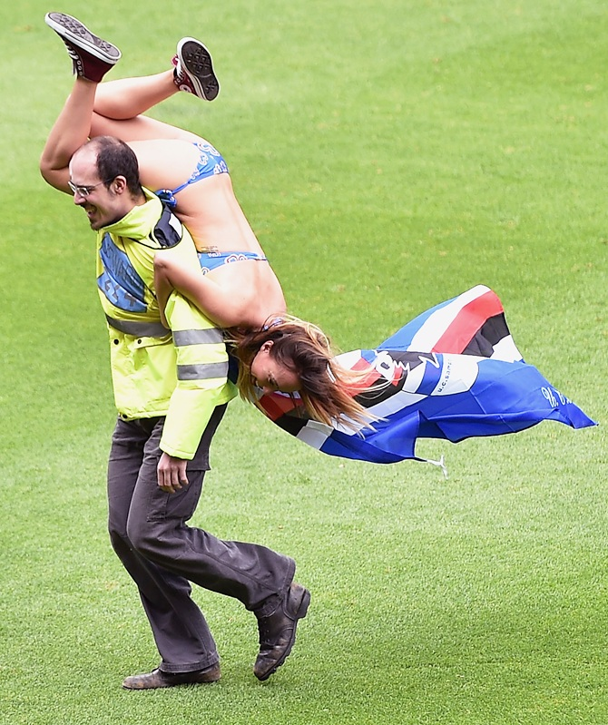 A fan of Sampdoria is carried off by a steward after running onto the pitch   during the Serie A match between UC Sampdoria and SSC Napoli