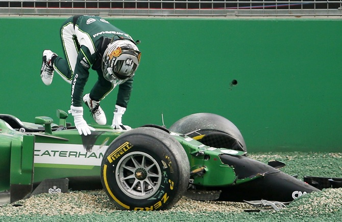 Caterham Formula One driver Kamui Kobayashi of Japan gets out of his car after colliding