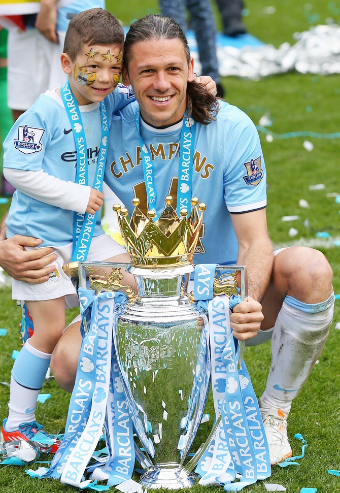Martin Demichelis of Manchester City poses with the trophy and his son