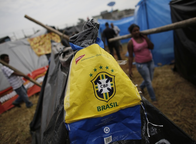 A bag with the logo of the Brazilian Soccer Confederation (CBF) is seen on a newly built shack of a member of Brazil's Homeless Workers' Movement (MTST) as people carry logs to build their own shacks at the 'People's World Cup' camp